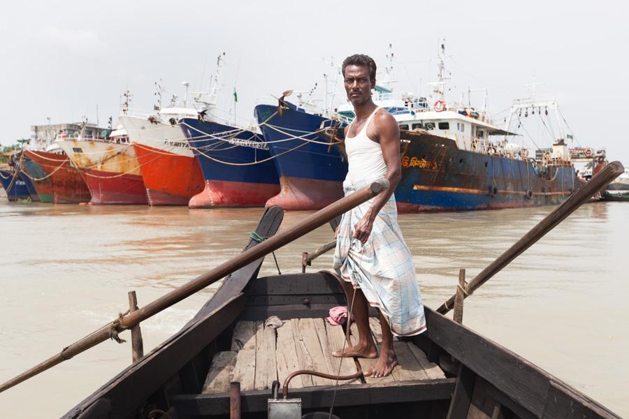 Bangladeshi boatman rowing his boat in front of old big ships near Sadarghat (River port) at Karnaphuli (Karnafuli) River, Chittagong, Bangladesh, Indian Sub-Continent, Asia