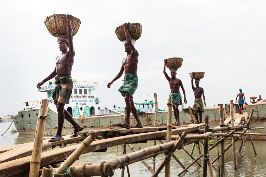 Bangladeshi men unloading goods from a river ship, a river quay on the east bank of Kirtonkhola River, Barisal District, Bangladesh, Indian Sub-Continent, Asia