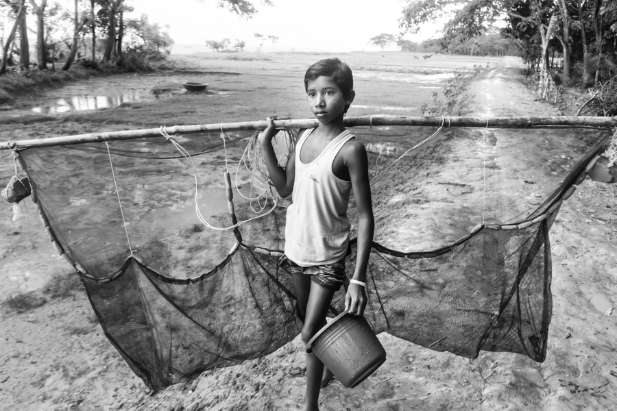 Boy with a fishing net and a bucket in his hands going to the river, Fishermen settlement near Chamdomban village, East Side of Kirtonkhola River, Barisal, Barisal District, Bangladesh, Indian Sub-Continent, Asia.