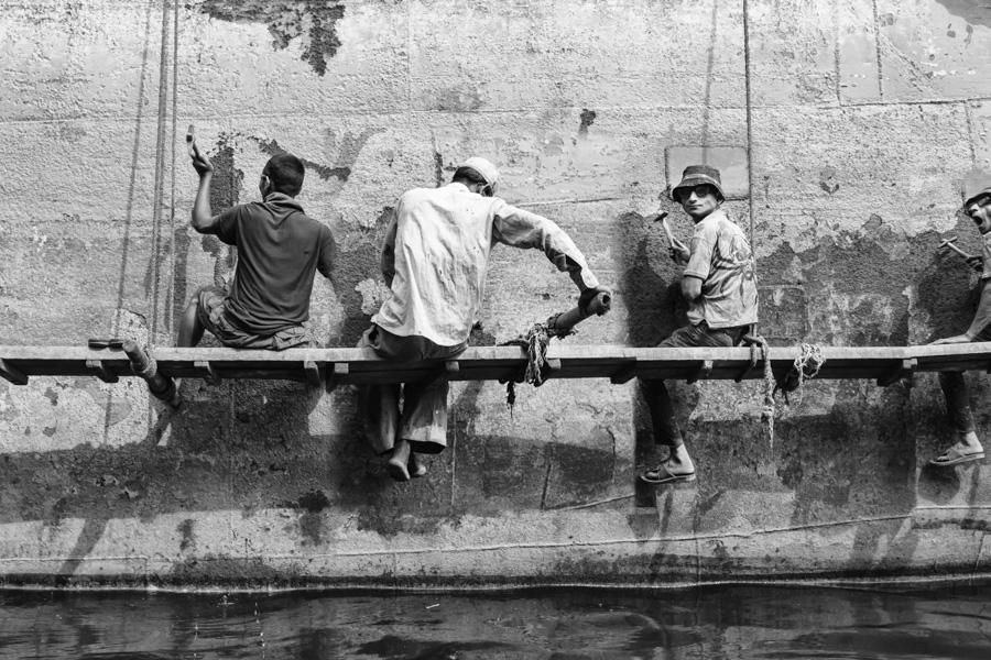 Men hammering away on the metal of the big ship at Dhaka Shipyard, Dhaka, Bangladesh, Indian Sub-Continent, Asia.