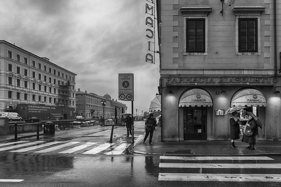 Two ladies chatting on a street in Trieste on a rainy day, Italy
