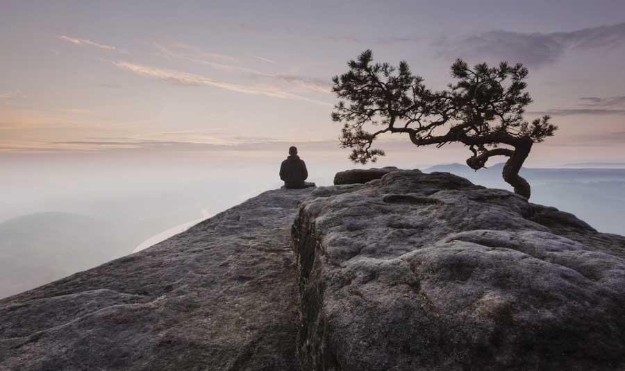 man sitting in beautiful foggy landscape
