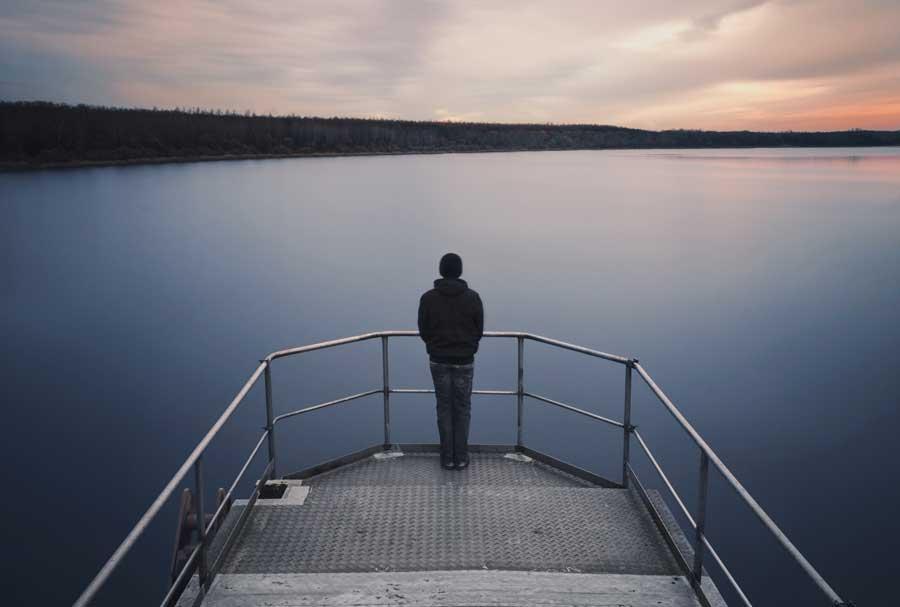 young man standing on lake