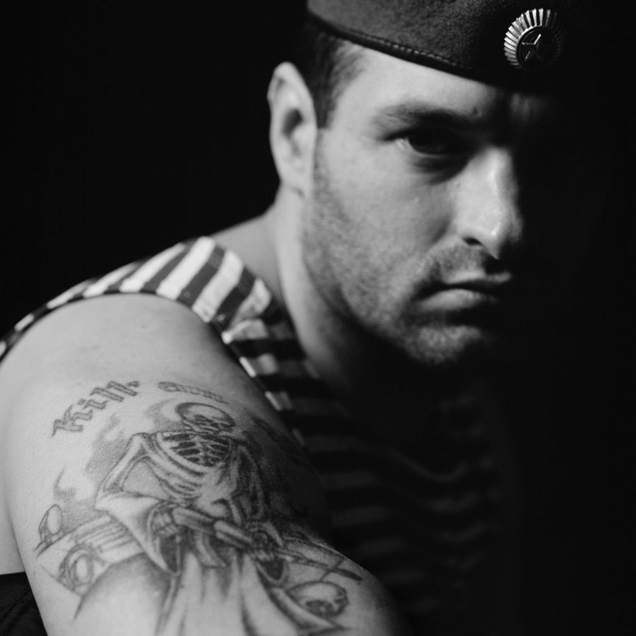 """Dmitri Beliakov - """"Maroon Beret"""" Igor Mokrov, veteran of two Chechen campaigns poses for a portrait and shows off his tattoo, which says """"Kill 'em All""""."""