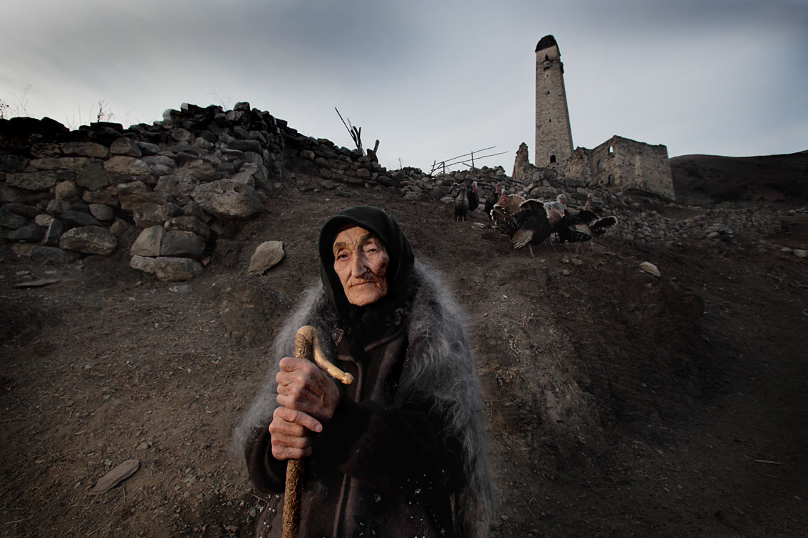 Ingush Tovsari Chakhkiyeva, 101 years poses beside the house she was deported from and where to she has come back from exile.