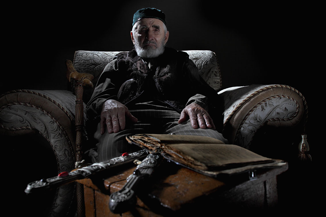 Ingush Isa Khashiyev, 80 years, poses with 100-years-old Koran and 116-years-old daggers, decorated with silver and precious stones, owned by his father and grandfather. Both relics were carefully hidden from the Soviets inside of mattresses through the course of exile.