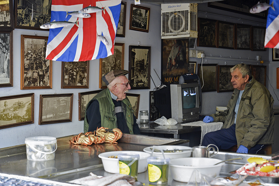 Disappearing Home-London East End's English community. 22. Mr Broomfield share a joke with his friend Tom at the George's Plaice, traditional East end fish shop, on 11th March 2015, London.