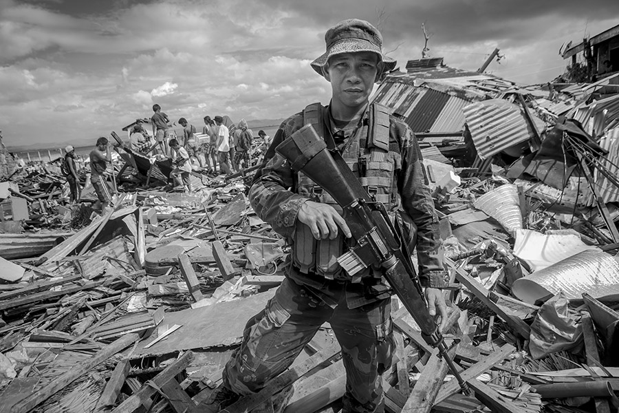 A heavily armed Philippino soldier looks at my camera after an attempt to detain some looters. I was walking through a side road close to the street of Magallanes, when all of a sudden we heard some women screaming that the remainings of their homes were being ransacked. A heavily armed military team rushed to the area , and despite their warnings that it could be quite dangerous to follow them since the looters could be armed and there was a most probable risk of confrontation, I run behind the team. We climbed over a pile of debris to see two groups of youngsters about to engage in a violent confrontation, so the military police pointed their arms at them and sorrounded them. Apparently, it all had started when a young girl had tried to gather some scattered dvds that belonged to a deceased person, and a member of the family of the deceased had tried to attack her exclaiming that the girl had been going in and out of a hole between the debris where the home of the victim had been before. The confrontation attracted many relatives and young friends of both families, and had it not been because of the military police intervention it could have escalated into a violent outburst. Since the policy of the Philippines Government regarding people who looted small items mainly for survival had been that one of a very understandable forgiveness, there were no detainees, although some of the teenagers had tried to steal more valuable items. Right after the typhoon ,gangs of people wandered about in panic like zombies and since they lacked water and food ,they engaged in looting and very soon there was a huge mob trying to ransack homes and stores, the same mob that went into the Robinsons supermarket and stole all kinds of items, including televisions, computers and washing machines.The situation was extremely dangerous, for as well all the prisioners of the Kashuagan Penal Colony (around 500) had been set free before the typhoon in order to save their lives and under the p