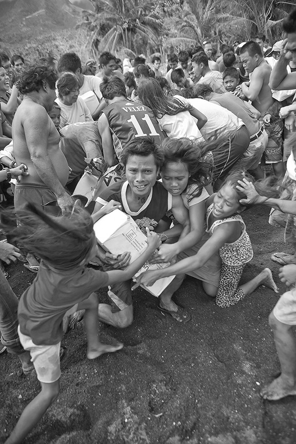As soon as the helicopter landed, the pilots were forced to follow a very strict security protocol. At first, one of the three pilots got off the helicopter and running towards the mob raised his hands to make them halt or move slower, and then he deposited a long line of plastic tape on the ground in order to mark the limits which the people were not supposed to trespass and where the relief food was going to be deposited. Of course this was easily said, but the reality was quite another; some of the people carried knives or batons and they were very excited and ready to bludgeon each other over food which meant their survival and that of their beloved ones. The people were ready to do anything to get hold on the food,and the protocol wasnt always being followed. Although they screamed their thanks to the pilots and smiled at them, the pilots also knew that if they didnt unload the food fast enough, the helicopter run the risk of being assaulted, so they had to hurry in a superhuman effort and communicating between themselves through a signal language (the helicopter sound is so loud that it is almost impossible to hear he human voice) both to direct the operation and to warn on any emergency situations, they proceeded to unload all the heavy packages of humanitarian aid. In order to prevent an assault to the helicopter, one pilot remained in the cabin ready for take off. As the load was being deposited on ground next to the tape, the crowd grew bigger and bigger and the bigger it grew , the more it seemed it was about to lose control, so the pilots, aware of that told me to rush into the helicopter and while we were taking off an extremely violent fight over the goods started to take place.The last pilot onboard even had some time before takeoff to shake hands with some of the people who felt extremely grateful towards them. Once we took off onboard of the helicopter the pilots started breathing oxygen from an onboard oxygen supply to avoid exhaustion.