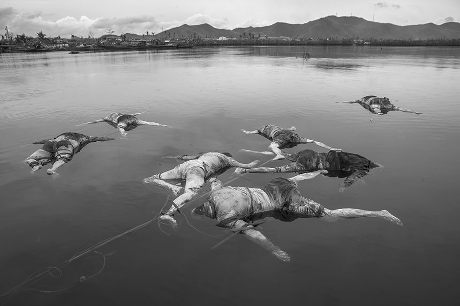 After the devastation created by the rise of the ocean levels, many people drowned at the area of San Jose (Tacloban City), which was one of the areas with most casualties.Improvised teams of fishermen volunteered to gather the corpses at the ocean and had them tied up together and secured by a rope tied to a stone laying at the bottom of the ocean, waiting for the body rescuers to come to pick them up and have them transported to mass graves. Most of them couldnt be recognized either because their relatives and friends were missing as well or because the bodies were beyond recognition. On the other hand the amount of casualties was so high that there was virtually no time for such a procedure (identifying the bodies by relatives or friends) and due to the high risk of spreading epidemics,the final decision was to have them immediately transported to mass graves, although an autopsy center gathered forensic data in an endless daily effort. That day it had been raining mildly and to an extent that there was a certain beauty , silence and calmness at the ocean, and the bodies floated motionless, as if it they had been deposited there on purpose, in an intermediate stage in between life and death and in communication with nature. I approached the bodies while standing on the top and mantaining the equilibrium on the thin canoe of two young fishermen and the sound of the drizzling rain and of their rowing paddles was the only sound to be heard.