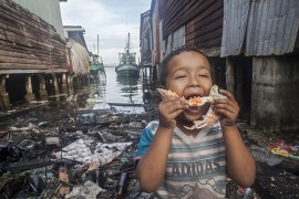 """Oblivious to the absolutely polluted and dirty marine surroundings, a  fisherman's child of the island of Koh Kong (Cambodia) proceeds to take a bite to the delicious piece of crab that his mother has boiled for him.   The once extremely beautiful peaceful, idyllic and transparent waters in where this fishing village  was established have been turned into a dumpsite throughout the years, and the locals, who were once able to fish close to the coast, find it harder and harder to harvest any captures, and in order to succeed they need to cover very long sailing distances and spend much more time out in the ocean.  As an added difficulty and due to the climate change, the waters have raised extremely high, flooding the village each year and threatening to make it disappear  beneath the waters.  Some of the locals have already relocated themselves inland Cambodia, well aware that the village is doomed, but  others , although they certainly do consider that alternative, keep waiting there , because as they say, """"they have no other place to go and no other way of earning their lives"""". In the beginning, as one of the old inhabitants said, they thought that mother nature could swallow all the waste they dumped there because it usually was always carried away by the waters, so none of them thought about pollution.  As the number of inhabitants increased due to the comparatively high status living status in relation to the inland living Cambodians, more and more wooden homes were constructed standing on pillars over the waters.  Curiously enough, no one thought about  any means of disposing their increasing waste or any sewage systems, so the continuous  impact of throwing of the garbage into the water plus the throwing of toxic liquids has not only changed the biodiversity surrounding the village, but has solidified into a permanent waste land, and the waters do not drag away the waste anymore."""
