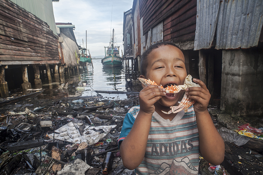 "Oblivious to the absolutely polluted and dirty marine surroundings, a fisherman's child of the island of Koh Kong (Cambodia) proceeds to take a bite to the delicious piece of crab that his mother has boiled for him. The once extremely beautiful peaceful, idyllic and transparent waters in where this fishing village was established have been turned into a dumpsite throughout the years, and the locals, who were once able to fish close to the coast, find it harder and harder to harvest any captures, and in order to succeed they need to cover very long sailing distances and spend much more time out in the ocean. As an added difficulty and due to the climate change, the waters have raised extremely high, flooding the village each year and threatening to make it disappear beneath the waters. Some of the locals have already relocated themselves inland Cambodia, well aware that the village is doomed, but others , although they certainly do consider that alternative, keep waiting there , because as they say, ""they have no other place to go and no other way of earning their lives"". In the beginning, as one of the old inhabitants said, they thought that mother nature could swallow all the waste they dumped there because it usually was always carried away by the waters, so none of them thought about pollution. As the number of inhabitants increased due to the comparatively high status living status in relation to the inland living Cambodians, more and more wooden homes were constructed standing on pillars over the waters. Curiously enough, no one thought about any means of disposing their increasing waste or any sewage systems, so the continuous impact of throwing of the garbage into the water plus the throwing of toxic liquids has not only changed the biodiversity surrounding the village, but has solidified into a permanent waste land, and the waters do not drag away the waste anymore."