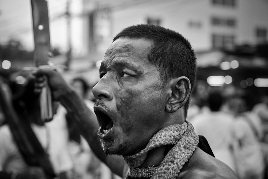 After having waited for the arrival of the Gods before a shrine and on the very first moment that the Gods have arrived, a medium has become in a deep state of trance, performing ritual movements , running in between the crowds holding a big machete, cutting his tongue and screaming with a fierce and deep voice. Although his behavior is violent, it is directed towards the evil spirits, since he is supposed to be possessed by a warrior God. Rolled around his neck is a whip that he will use both against evil spirits and to bless the worshippers.