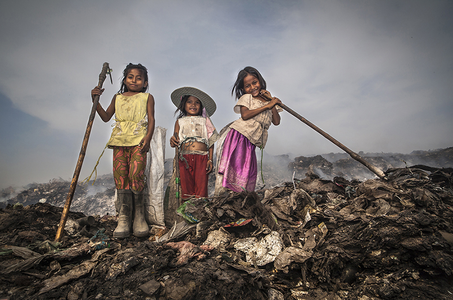 Having the privilege of being able to attend school, these three little girls had just arrived to their slums and without changing their clothes they put on their boots, picked up their hoes and their sacks and went directly to try to earn some extra income at the dumpsite. As usual and before committing themselves to their scavenging chores, they tied their sacks around their waists, and then proceeded happily, as if it was a game, chattering and joking between themselves. The only issue is that their situation is a serious one; they remain alone and vulnerable, they will probably work until night, and a close look to some of the gear they wear or lack wearing it will clarify better the situation they are about to face. For one reason, the youngest one presents the key to her wooden slum hanging from her neck , which means that no one will be waiting for her upon her return for dinner time or even throughout the night. A further look shows that they do not wear any protecting gloves, which are extremely important for the scavengers, specially when the sun starts to go down and the light becomes scarce and they cannot see well. They are continuously digging and picking up stuff which might well have cutting edges , or worst of all ; they can unknowingly pick up medical waste or piercing contaminated needles, which happen to be thrown all over the place. On the other hand they are going to be working in an area which has been recently set on fire, and the toxic fumes continue to exhale from the piles of waste, and they will also be walking over piles of coals and burning embers which are prone to collapse underneath them. Under the extreme heat coming from the ground and their continuous walk wearing their rubber boots without socks, their feet become swollen ,sweaty and blistered. At some places the fire is still high, and if they dare to go through the paths delimited by the fire -particularly at night- due to the smoke they can easily become intoxicated and
