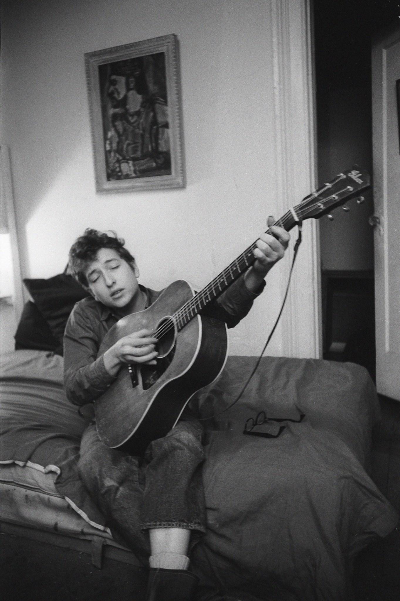 Bob Dylan playing guitar on his bed in his apartment, 161 W 4th St, Greenwich Village, NYC, 1961 (c) Ted Russell / Govinda Gallery