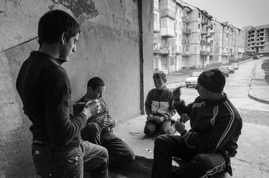 "Four children playing ""Cruce"" (a card game) at the entrance to a building in the neighborhood ""New Town"" in Anina."