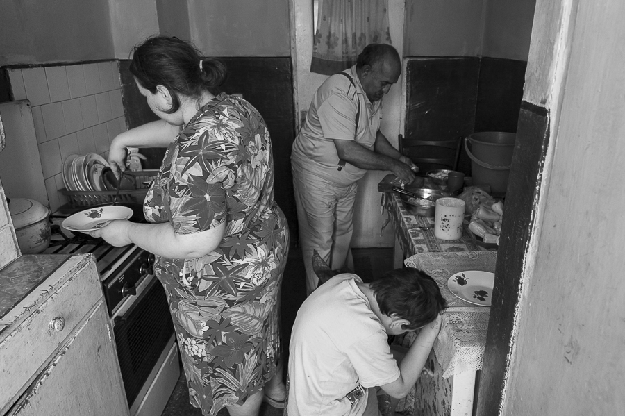 Ion Cojocea with his daughter and one of his grandchildren, preparing lunch in the kitchen of the apartment.