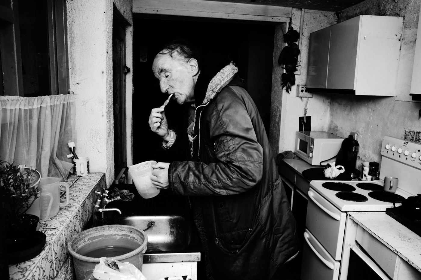David brushing his teeth in the kitchen sink before embarking on his daily walk.