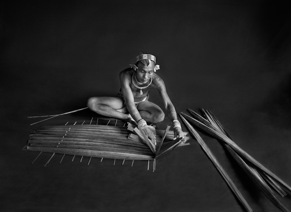 Teureum, sikeirei and leader of the Mentawai clan. This shaman is preparing a filter for sago, with the leaves of this same sago tree. Siberut Island. West Sumatra. Indonesia. 2008. Photograph by Sebastião SALGADO / Amazonas images