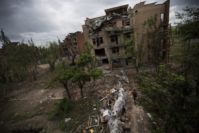 "A fighter of ""Donbas"" battalion dodging sniper' bullets beside a ruin of ex-sanatorium, destroyed by the Russian artillery, June 26 2015, Shirokino, East of Ukraine"