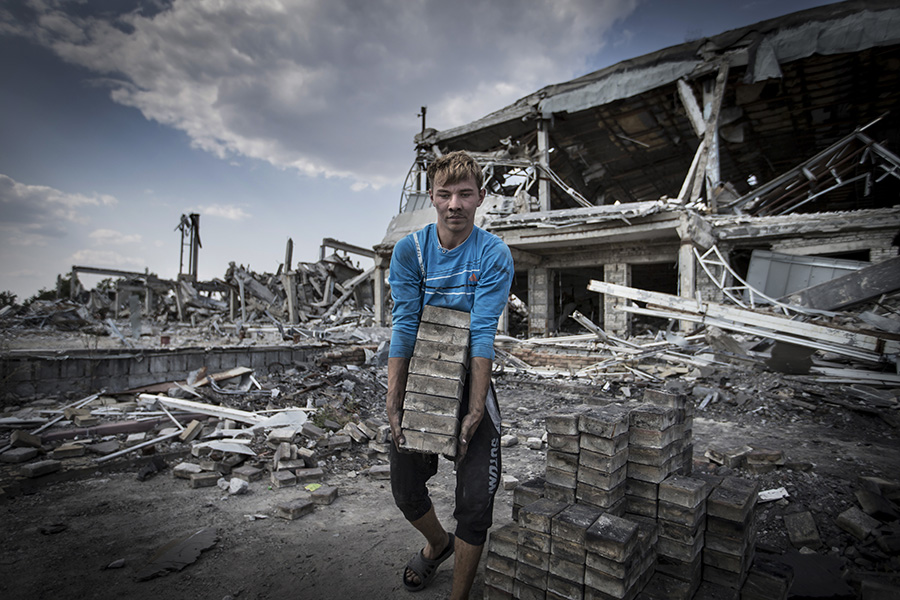 The bricks collectors working at the territory of ruined international terminal of Luhansk airport. Each brigade need a license from one of competing battalions, headed by the pro-Russian warlords, leaders of the separatist's fighters, August 28th 2015, Luhansk, Eastern Ukraine Photographer: Dmitri Beliakov