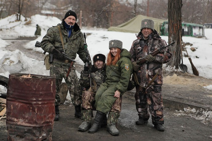 Cossack family - a father, a son and his girlfriend and a grandfather pose for a family photo on the rebels' check-point. The war-torn Donetsk and Luhansk regions, with their industrial factories, coal mines and steel mills, until recently comprised 16% of Ukraine's GDP. Now workers, such as this cossack Gennady, 58, have turned their ancient guns against Kiev' governement, December 08 2014, Pervomaisk, Eastern Ukraine. Photographer: Dmitry Beliakov/ for Der Spiegel