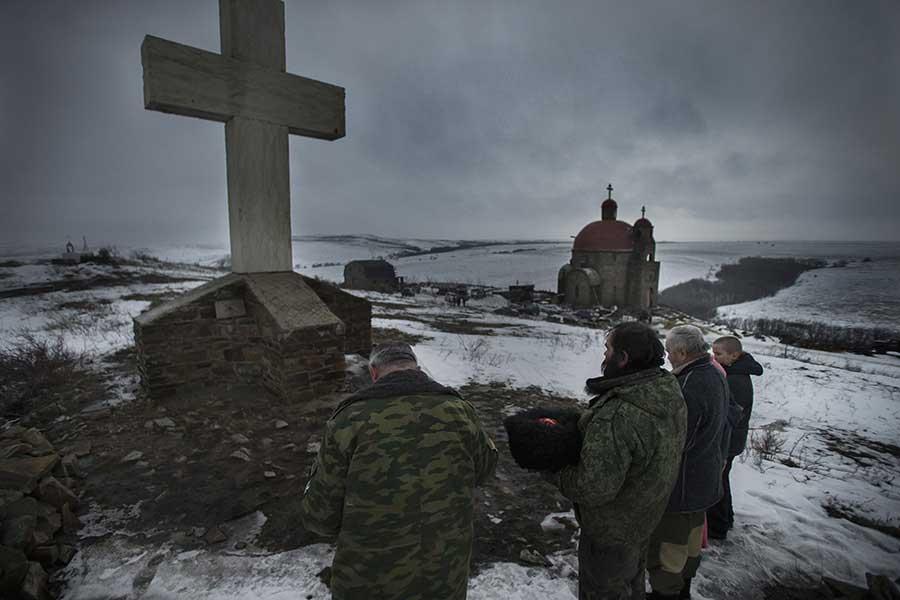 Pro-Russian militants pray before going frontline, Lutugino, Luhansk area, Ukraine, January 30 2015. Photographer: Dmitri Beliakov