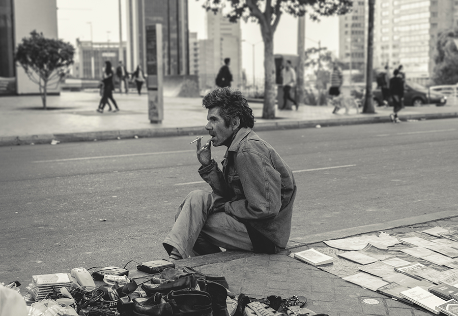 Every sundays in the downtown of Bogota, people usually go to buy used stuff. In the photo, a seller is smoking a cigarette while he looks people walking on the avenue.