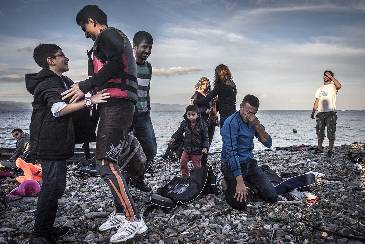 Refugees reacts after arriving safely by broken raft to Lesbos island, Greece, Monday October, 12, 2015. (Photo Sergey Ponomarev for The New York Times)