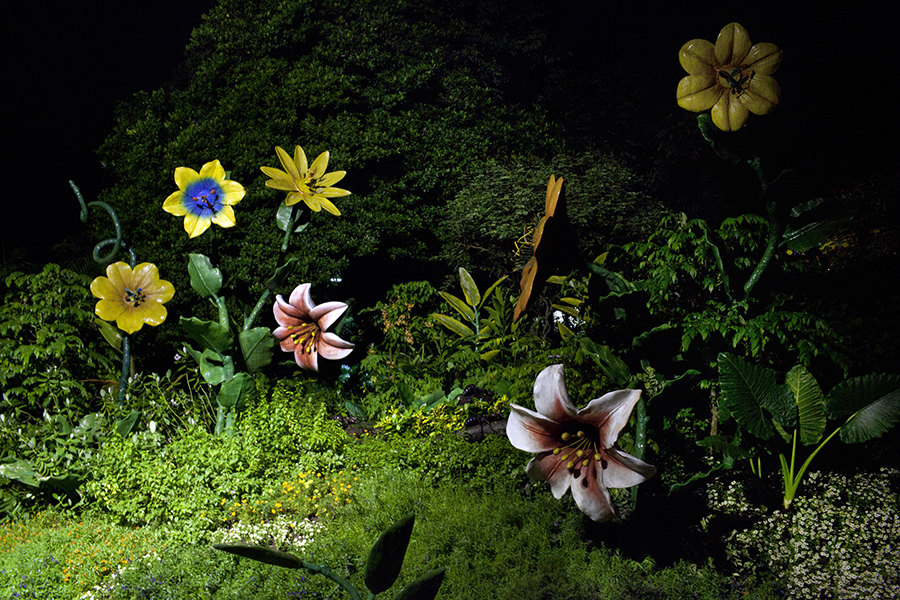 At nightfall, large fantastical ceramic flowers illuminate the jungle slopes of Singapore's man-made resort island, Sentosa, which draws five million visitors a year.