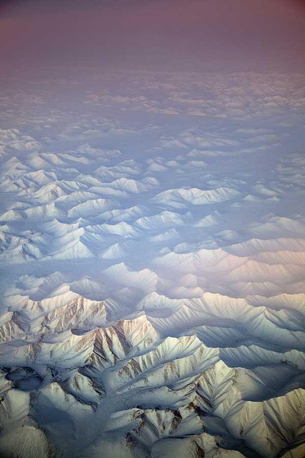 Arctic morning light on a snow-capped Siberian mountain range bordering the Chukchi and Bering Seas.