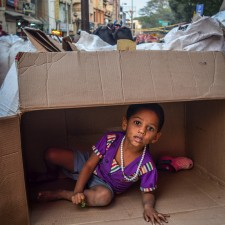 A kid makes her own play area in descarded box