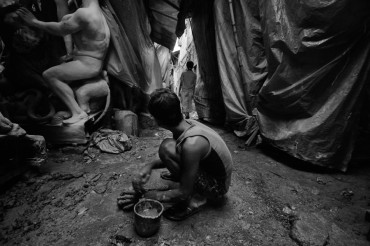"A junior artist is busy with his work in the filthy lanes of ""Kumartuli"", the potter's hub in Kolkata. Artisans squat on the street, kneading the clay or working on idols here."