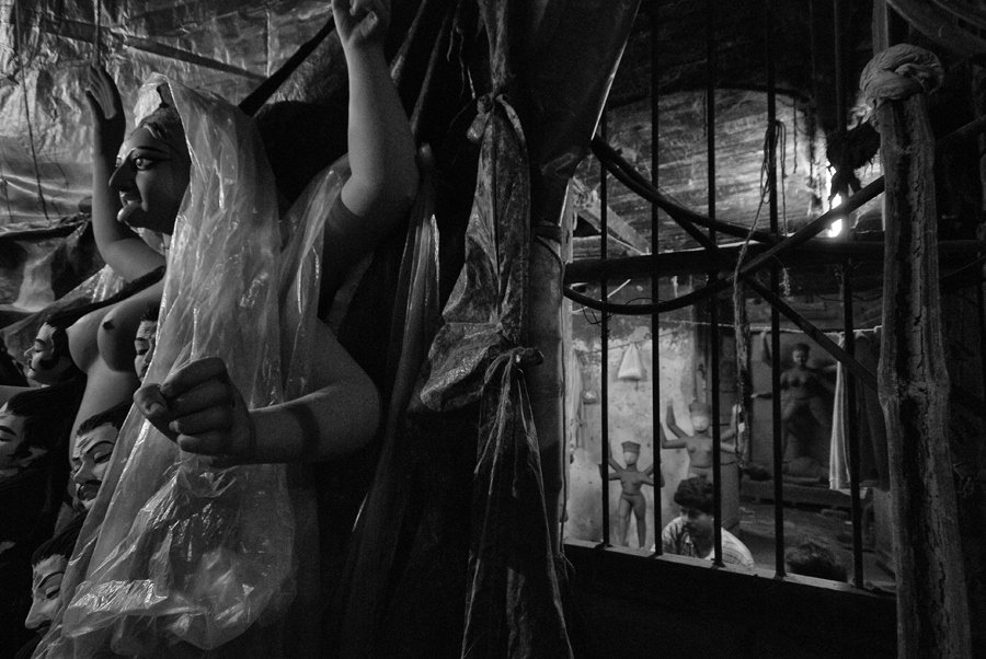 Goddess 'Kali' stands on lone guard in a dark alley of Kumartuli, while behind her the room of an artisan depicts his deplorable economic condition.