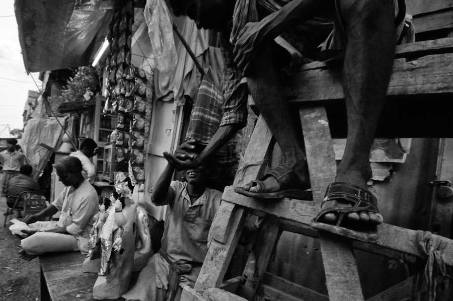 During the Puja season, the 'extra hands' come from different parts of Bengal because making the idols of Goddess Durga is a grand affair. Some of those assistants are enjoying 'Khaini', a popular and low priced tobacco medium.