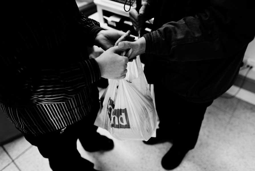 Supermarket staff handing David his bag of shopping.
