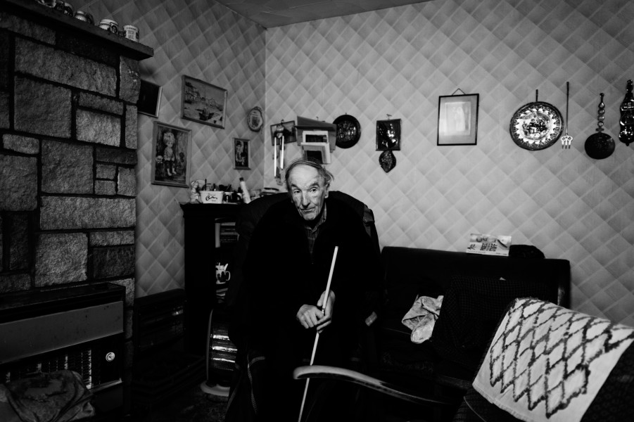 Alone in his front room, David sits next to his late Mother's chair, since her passing, now empty.