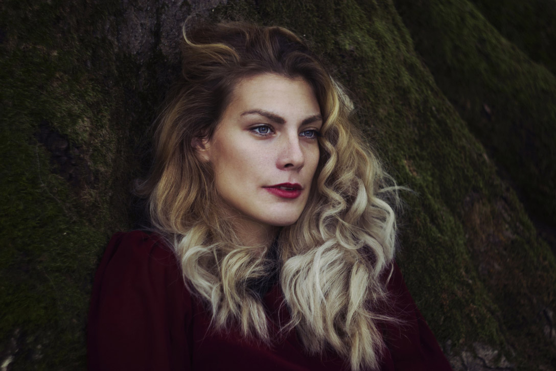 In this image with Chiara, the red of her lips and shirt, as well as the green moss on the tree and her blonde locks, made a good base for a dark fairytale-like photo.