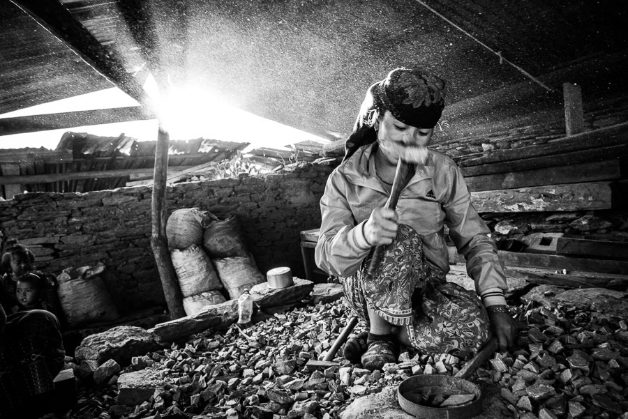 A woman crushing rocks into gravel with a hammer; this material is needed for constructing houses. It is hard and laborious work, which they do for several hours every day. Barpak, in Gorkha District, the epicentre of the earthquake of 25 April 2015.