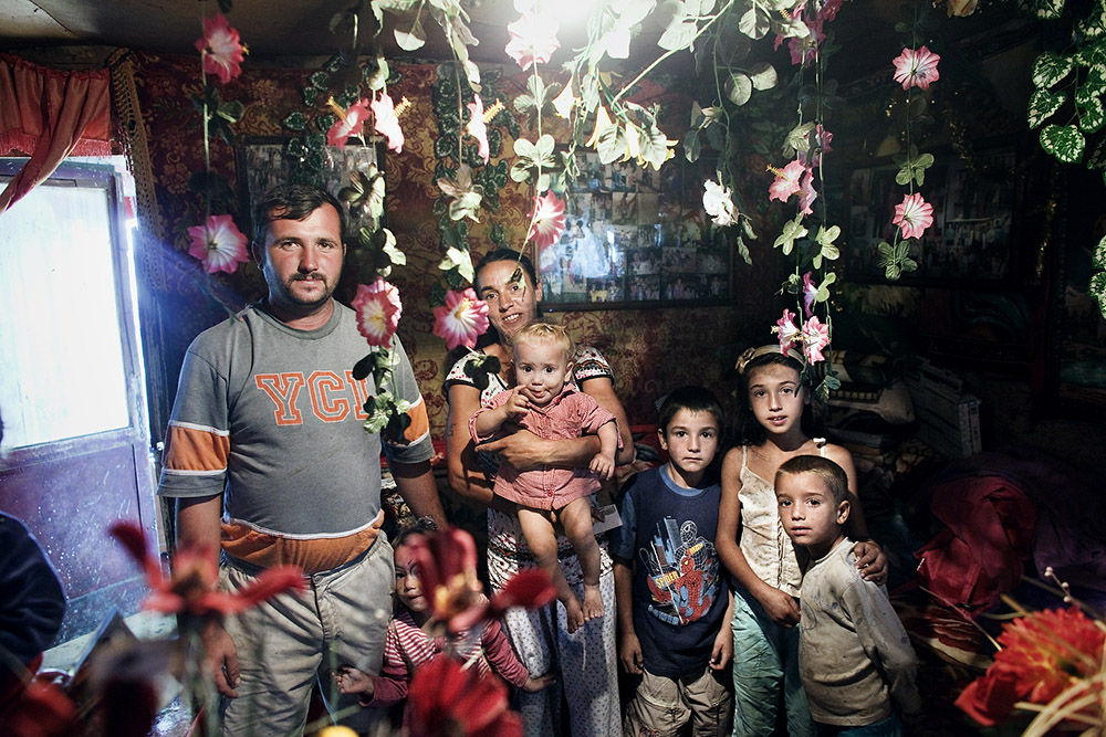 Romanians of roma origins pose for the camera inside their ramshackle dwelling, as seen on Craica, an informal roma settlement in Baia Mare, on September 24, 2011. Some of these settlements, like the one on Craica, date back to early 90's. They where always tolerated by the authorities who verbally encouraged Romas to build in the area while giving reassurance that nothing bad would ever happen to them. Yet, today, while campaigning on a hate ticket, the same authorities are planning forced evictions without other reasons than ethnic cleansing of the cities.