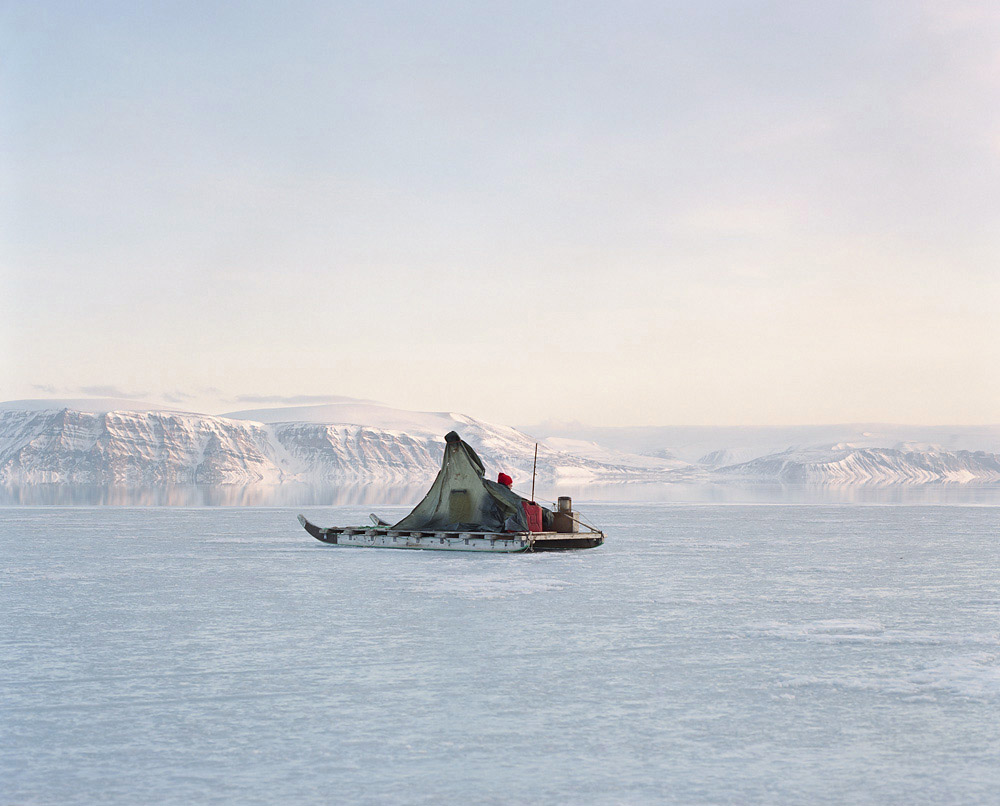 At the frontier between sea ice and open water, about forty kilometers from the closest settlement in the northermost area of Greenland, a hunter watches for seals from his sled. Meanwhile, the other hunters are gone hunting from the boat.