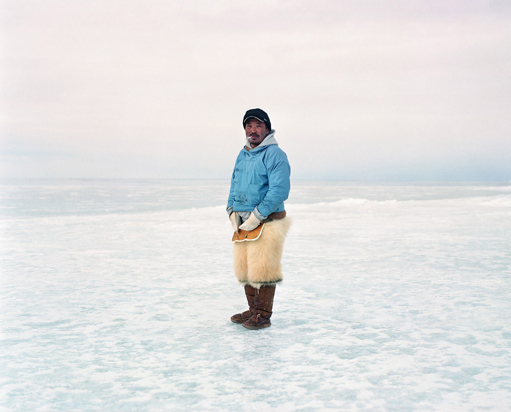 "A few meters from a hunting camp on the sea ice, Frank's outfit reflects current evolutions in cloth- ing: although ""kamik"" (traditional boots) and pants made from animal hides and furs are still used during sledges journeys and stays on the ice, more modern materials are also appearing. After the camp has woken up, it is time to fill the water bottles with drinking water. Hunters cut ice blocks from the icebergs stuck in the sea ice, and let them melt over a camping stove. The hunt will only starts at nightfall, and until them the jour- ney must continue further on the sea ice until the extremity is reached."