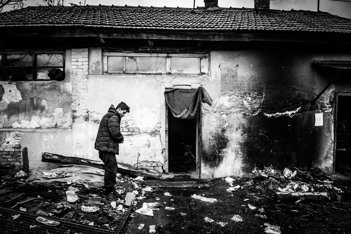 Man at the front of abandoned building, which is his temporary shelter, at the back the main train station Serbia, Belgrade.