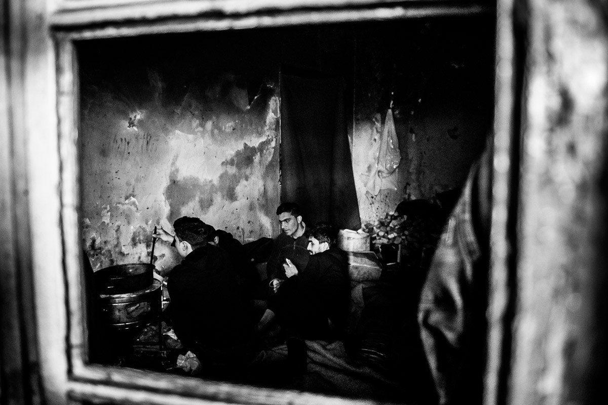 "Man during cooking. View through a window into one of the ""rooms"" in abandoned warehouse in Serbia, Belgrade."