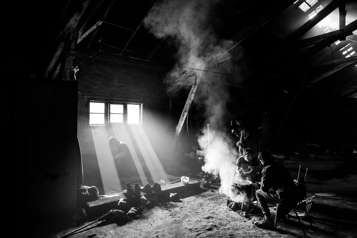 Men gather around a fire at the barracks ,during the meal. Serbia, Belgrade