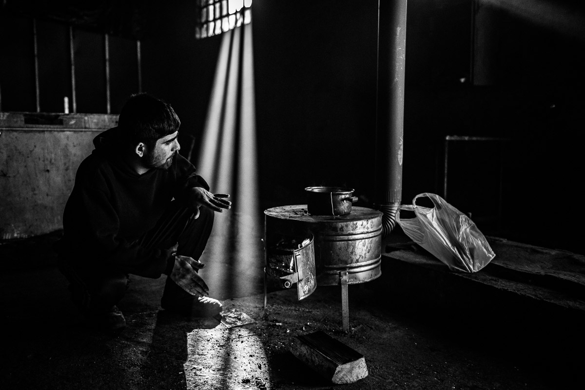 Man makes tea on the makeshift stove and tries to warm himself inside a derelict warehouse in Serbia, Belgrade.