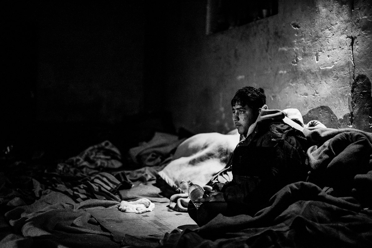 Stranded refugee inside derelict warehouse where is cold, so people have to use blanket to warm themselves, Serbia- Belgrade.