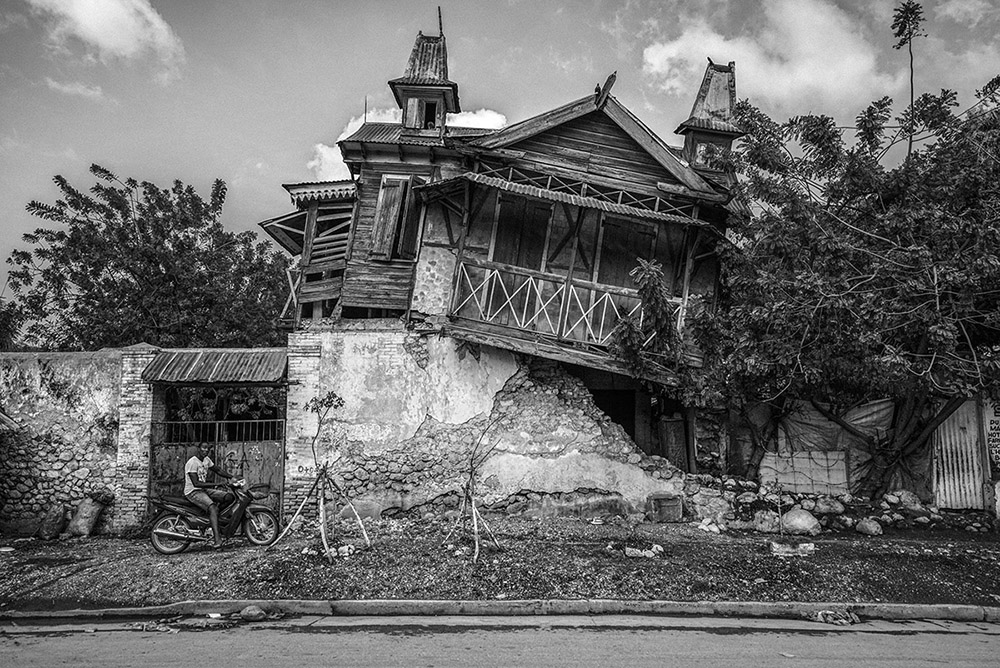 'THE EPICENTER'- LEOGANE, HAITI. JANUARY 19, 2015. An unposed moment of a young man on his motorcycle outside the crumbling ruin of a building in Leogane, some 25 miles from the Haitian capital of Port-Au-Prince. Following the devastating 7.0 earthquake in January 2010, a United Nations disaster-response assessment team reported that this was 'the worst-hit area' with over 25,000 deaths and upward of 80% of all concrete structures destroyed.
