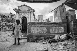 'MOURNING IN THE CEMETERY' - PORT-AU-PRINCE, HAITI. JANUARY 12, 2015. On the fifth anniversary of the devastating earthquake, a young child stands to the side of her mourning mother who lies weeping nearby in the Grand Cemetery of Port-Au-Prince, Haiti.