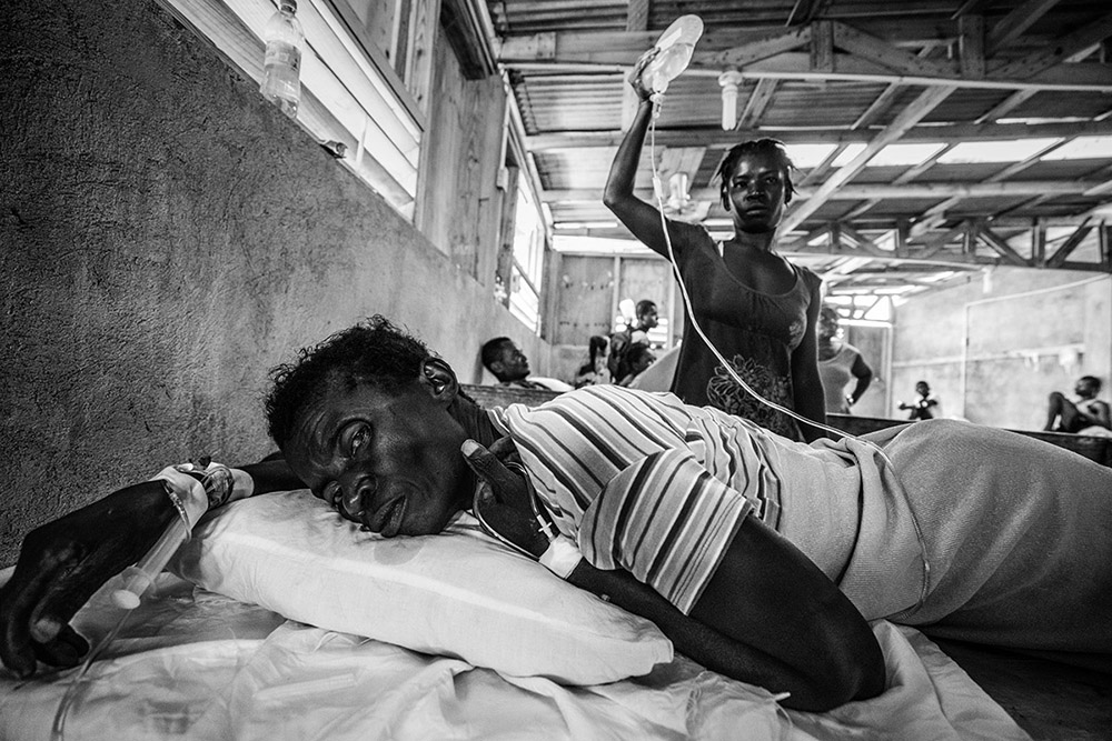 'CHOLERA AFTER HURRICANE MATTHEW' - LES CAYES, HAITI. OCTOBER 15, 2016. A tired relative of a cholera victim holds up an intravenous plastic bottle in Cholera Treatment Center in downtown Les Cayes - a town largely cut-off from road supply routes following Hurricane Matthew. There were no IV stands available in the ramshackle clinic from which to hang the dwindling stock of much-needed hydration bottles.